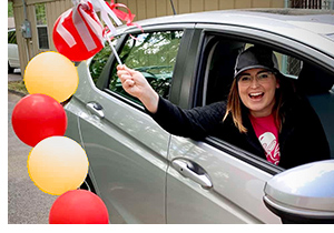 Celebrating Customer Service Week by delivering gifts in a car decorated with Dream Team balloons and pennants.